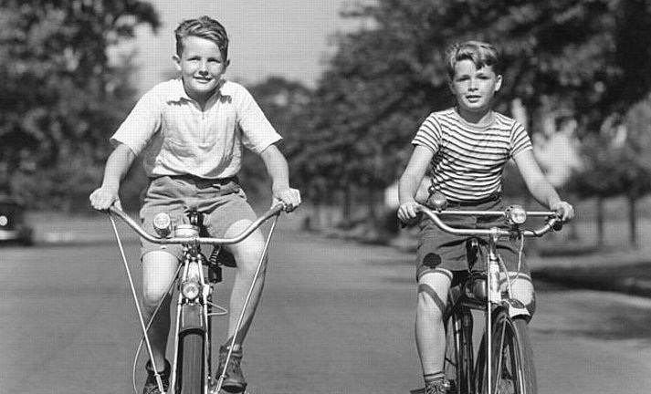 boys wearing shorts and riding a bike
